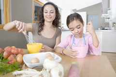 Mother and Daughter Beating Eggs in Kitchen Stock Photos