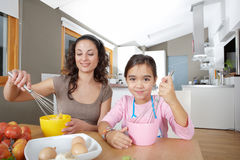 Mother and Daughter Beating Eggs in Kitchen Stock Images