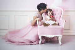 Mother and daughter a beautiful and happy pink interior with vintage chair and balls in beautiful dresses royalty free stock photography