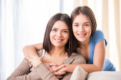 Mother and daughter. Beautiful mother and her cute daughter smiling and posing at home Stock Images