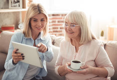 Mother and daughter. Beautiful mature mother and her adult daughter are drinking coffee, using a digital tablet and smiling while sitting on couch at home Royalty Free Stock Photography