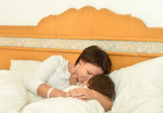 Mother with daughter in bed Stock Photos