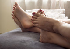 Mother and daughter on the bed at home with their feet showing Stock Photography