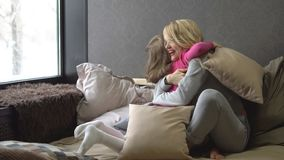 Mother and daughter on the bed playing with pillows and hugs. Slow motion stock video