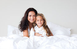 Mother and daughter on bed smiling at camera Royalty Free Stock Photography