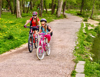 Mother and daughter on bicycle. Bikes cycling family. Stock Photo