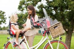 Mother and daughter with bicycle in park. Portrait of mother and daughter with bicycle in park stock photos
