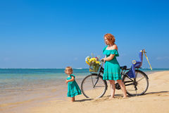 Mother with daughter with bicycle on the sea sand beach Royalty Free Stock Photo