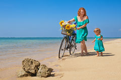 Mother and daughter with bicycle on the sea sand beach Royalty Free Stock Images