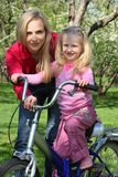 Mother with daughter on bicycle in spring stock photos