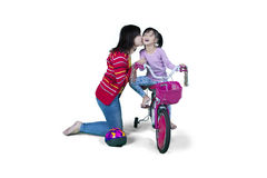 Mother and daughter with bicycle in studio Royalty Free Stock Image