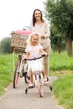 Mother and daughter with bicycles in park. Full length portrait of mother and daughter with bicycles in park stock photography