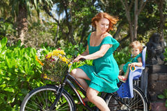 Mother and daughter bicycling and carrying flowers Royalty Free Stock Photography