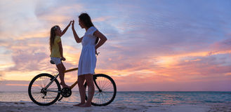 Mother and daughter on a bike stock images