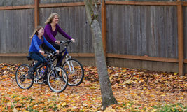 Mother and Daughter on Bike Path. A mother and her pre-teen daughter have fun together as they ride on a bike path strewn with fall leaves Stock Photo