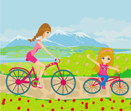Mother and daughter biking in the park Stock Photo