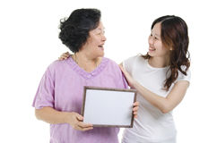 Mother and daughter with blank board Stock Photo