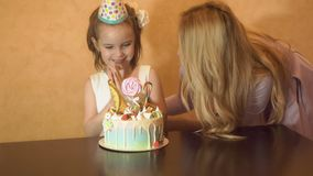 Mother and daughter blow out candles on a birthday cake. the birthday of a little girl. the birthday girl in a festive hat at a ch. Ildren`s party Stock Photos