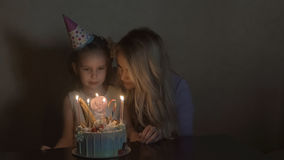 Mother and daughter blow out candles on a birthday cake. the birthday of a little girl. the birthday girl in a festive hat at a ch. Ildren`s party Royalty Free Stock Photos