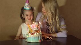 Mother and daughter blow out candles on a birthday cake and making a wish. the birthday of a little girl.  Stock Image
