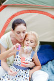 Mother and daughter blowing bubbles Stock Images