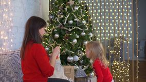 Mother and Daughter Blowing Bubbles near the Christmas Tree. Mother and Daughter Blowing Bubbles in the Modern Room near the Christmas Tree stock video footage
