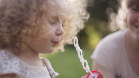 Mother and daughter blowing bubbles outdoors in summer sunshine. Red-haired mom and curly-haired daughter blow bubbles in the Park stock video