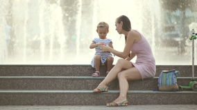 Mother and daughter blowing bubbles in the park stock video footage