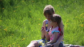 The mother with daughter blowing on a dandelion. Sitting in the flower meadow stock footage