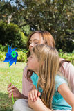 Mother with daughter blowing pinwheel in the park Royalty Free Stock Images