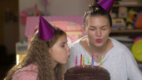 Mother and daughter blows out candles on birthday cake at party and make a wish