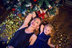 Mother and daughter in blue dresses lie under the Christmas tree. With gold confetti Royalty Free Stock Photos