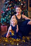 Mother and daughter in blue dresses sitting. The Christmas tree Royalty Free Stock Images