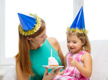 Mother and daughter in blue hats with cake Royalty Free Stock Photos