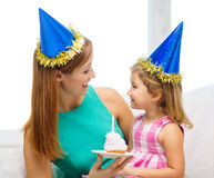Mother and daughter in blue hats with cake Royalty Free Stock Photo