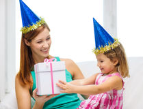 Mother and daughter in blue hats with favor horns Stock Photo