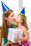 Mother and daughter in blue hats with favor horns Royalty Free Stock Photo