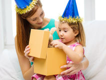 Mother and daughter in blue hats with favor horns Stock Photos