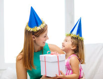 Mother and daughter in blue hats with favor horns Royalty Free Stock Image