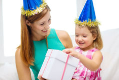 Mother and daughter in blue hats with gift box Royalty Free Stock Image