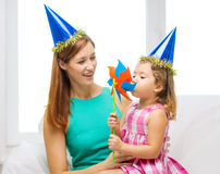 Mother and daughter in blue hats with pinwheel Royalty Free Stock Images