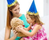 Mother and daughter in blue hats with teddy bear Stock Photos