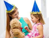 Mother and daughter in blue hats with teddy bear Royalty Free Stock Image