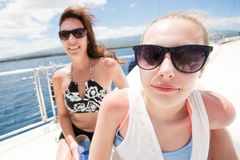 Mother and daughter on a boat at sea stock images