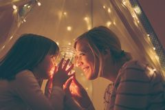 Mother and daughter bonding. Mother and daughter sitting in a tent, holding a jar with christmas lights and telling stories. Focus on the mother stock photo