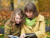 Mother and daughter with a book. Mother and her teenager daughter sitting with a book on a bench in an autumn park Royalty Free Stock Photography