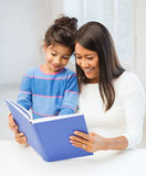 Mother and daughter with book. Family, children, education, school and happy people concept - mother and daughter with book Royalty Free Stock Image