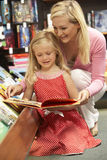 Mother and daughter in bookshop. Looking at a book Royalty Free Stock Photo