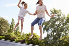 Mother And Daughter Bouncing On Trampoline Together Stock Photos