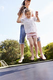 Mother And Daughter Bouncing On Trampoline Together Royalty Free Stock Photos